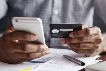 man holding credit card and mobile phone